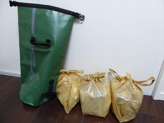 壁に立てたバッグとスーパーのビニール袋に入れた防災グッズ