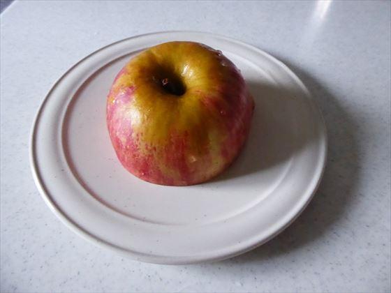 半分に切ったりんごを切り口をしたにして皿に置いている様子