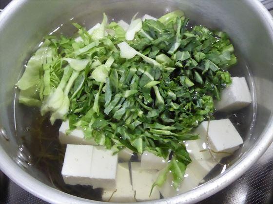 鍋にしわしわになった外側の葉と豆腐が入っている様子
