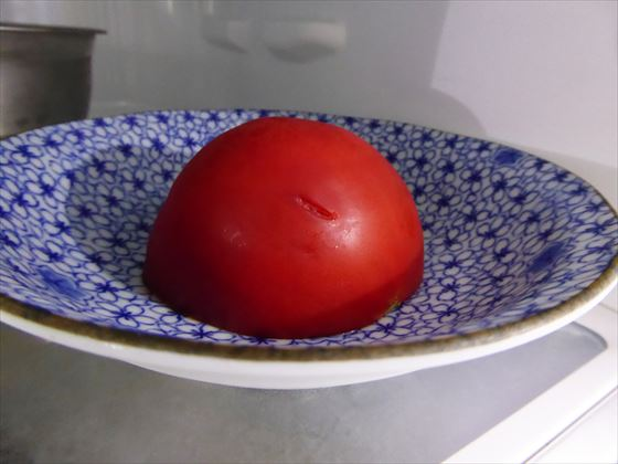 半分に切ったトマト、切り口を下にして冷蔵庫で保管している様子