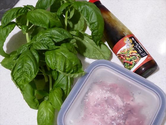 ガラス容器に入った豚肉、オイスターソース、バジルの束