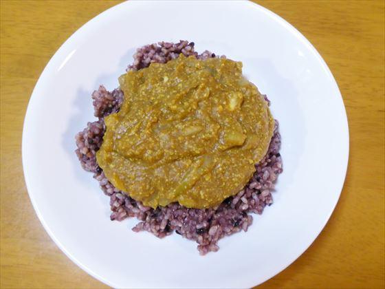 黒米ご飯にカレーがのっけた様子、白い皿
