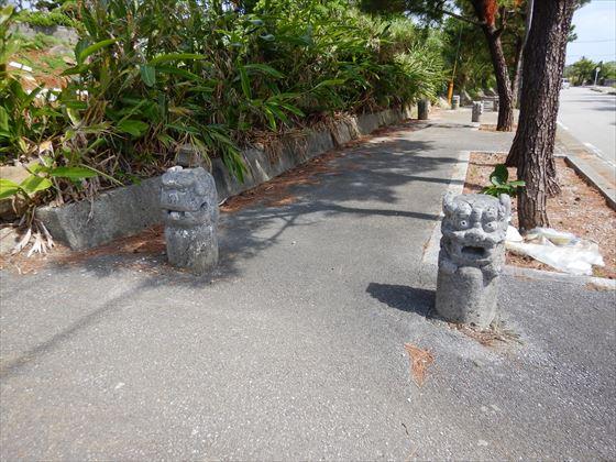 歩道にあるシーサーの形をした車止め 色が黒いシーサー