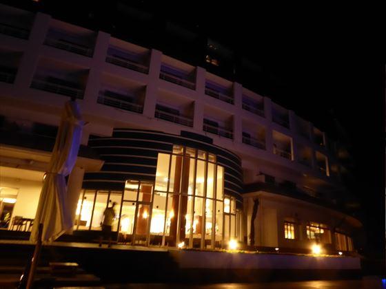夜のプールサイドからホテルを眺める