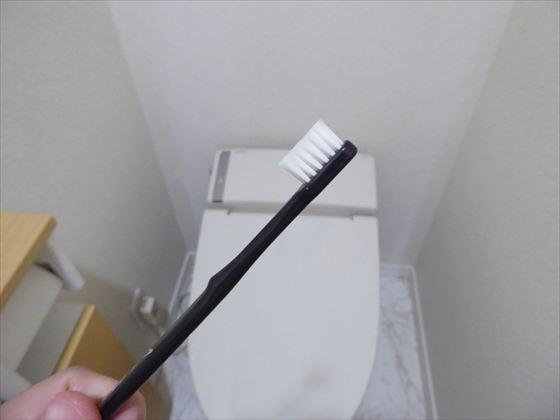 使い古した歯ブラシでトイレ掃除をするところ