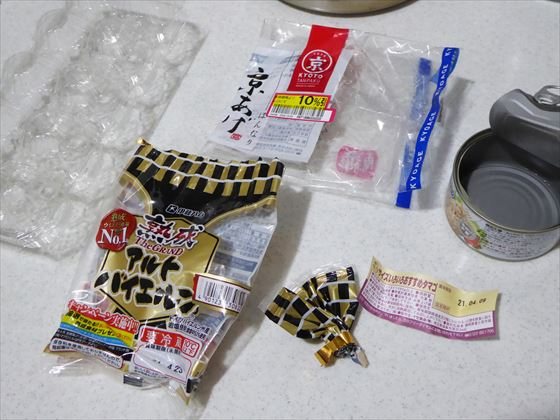 卵のパック、卵の賞味期限が書かれた紙、油揚げの袋、ウインナーの袋、ツナ缶の缶