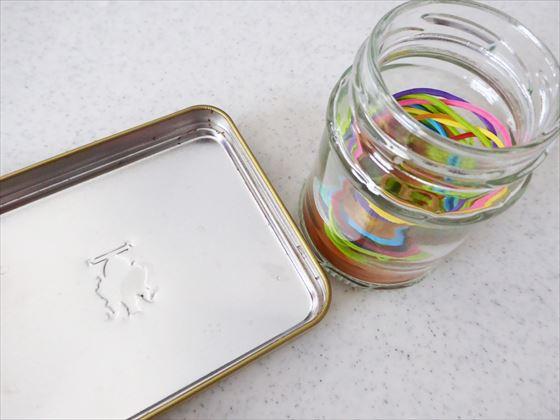 四角い缶の蓋と瓶に入った輪ゴム