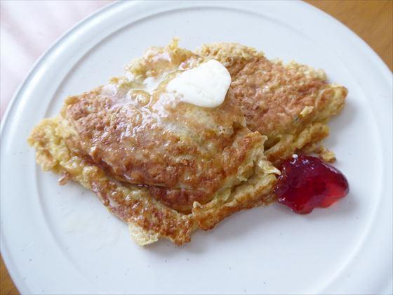 パンケーキを皿に盛って、バターと苺ジャムをのせたところ