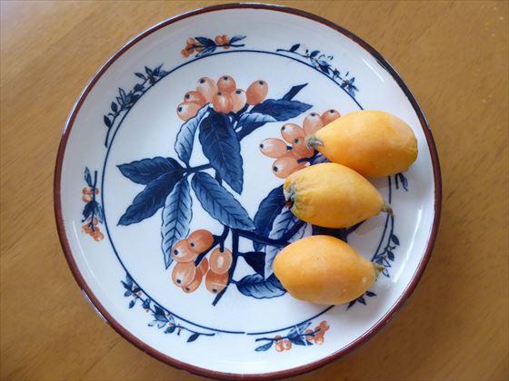 ビワの絵が描かれた皿にのったビワ3個