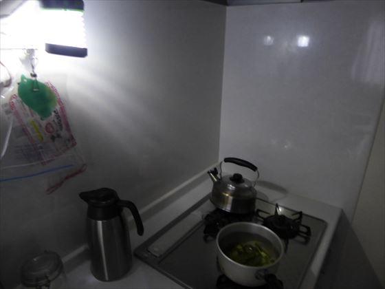 ソーラーランタンのライトで照らされているコンロ、ピーマンを蒸し煮にしている様子