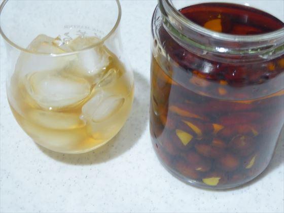 瓶に入ったビワ種酒とグラスに入れたビワ種