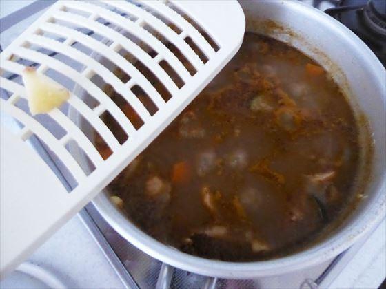 鍋に入ったカレーにジャガイモをすりおろしている様子