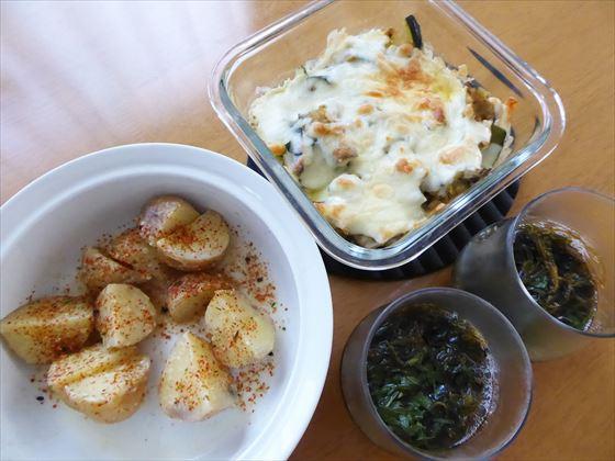チーズ焼きと容器に入ったジャガイモの味噌煮、グラスに入ったもずく酢