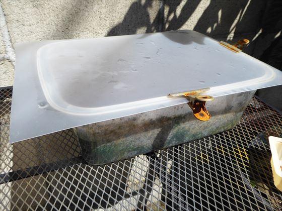 プラスチック容器にプラスチックの板を被せて、クリップで留めている様子
