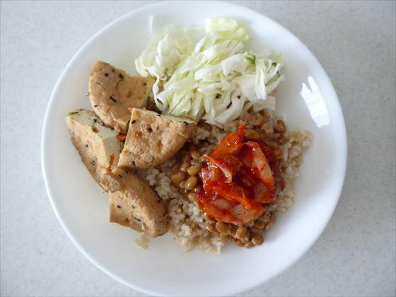 皿に盛った玄米、キャベツ、がんも、納豆キムチ