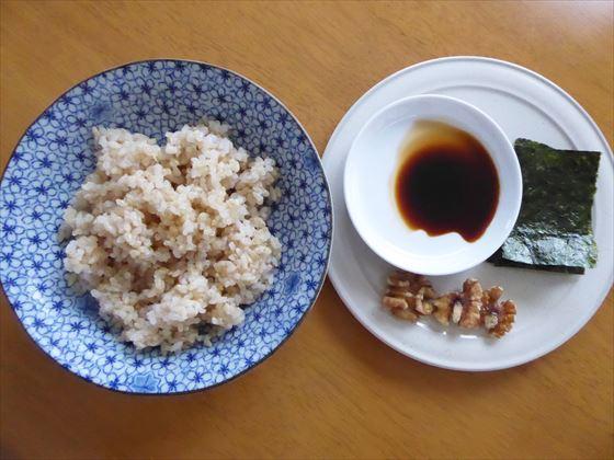 青い皿にはいった玄米と小皿にのった海苔とクルミ