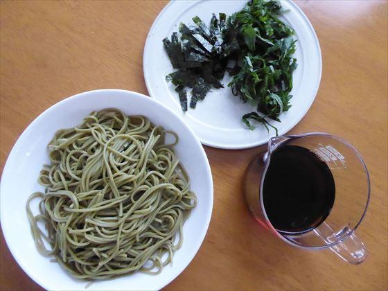 皿に盛った茶蕎麦と平皿に盛った薬味(海苔と青じそ)