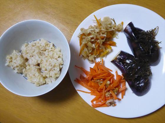 茶碗に入った玄米、白い皿に盛った焼きナス、人参の甘酢和え、切り干し大根