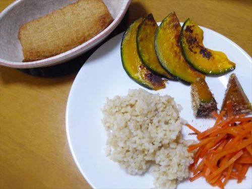 耐熱容器にのせたさつま揚げ、皿に盛った玄米やかぼちゃのソテー